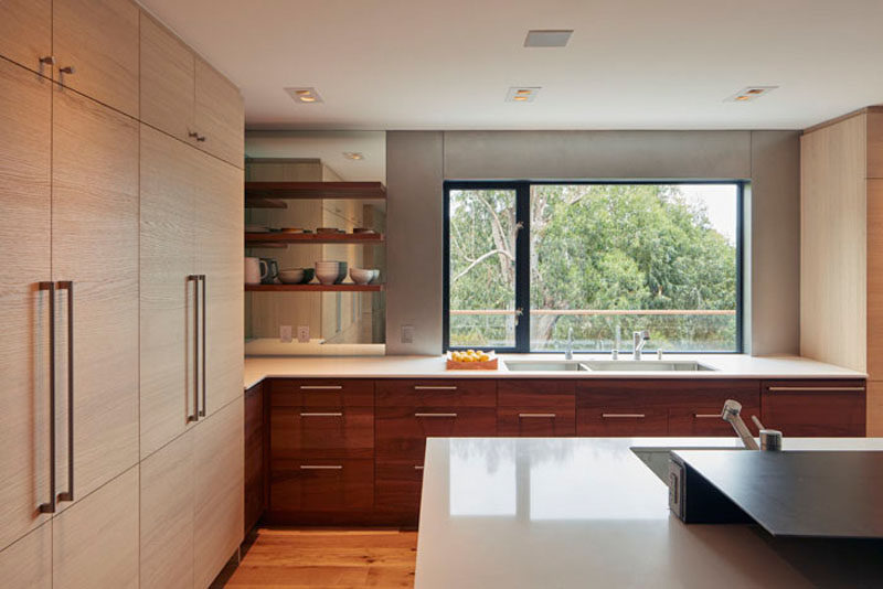In this modern kitchen, dark and light wood cabinetry are featured, while a window frames a view of the trees, and a mirror reflects the floating shelves and light, making the corner brighter.