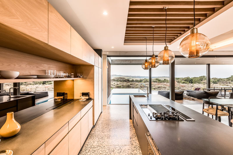 The long kitchen island draws your eye towards the swimming pool outside. #ModernKitchen #KitchenDesign #WoodCabinets