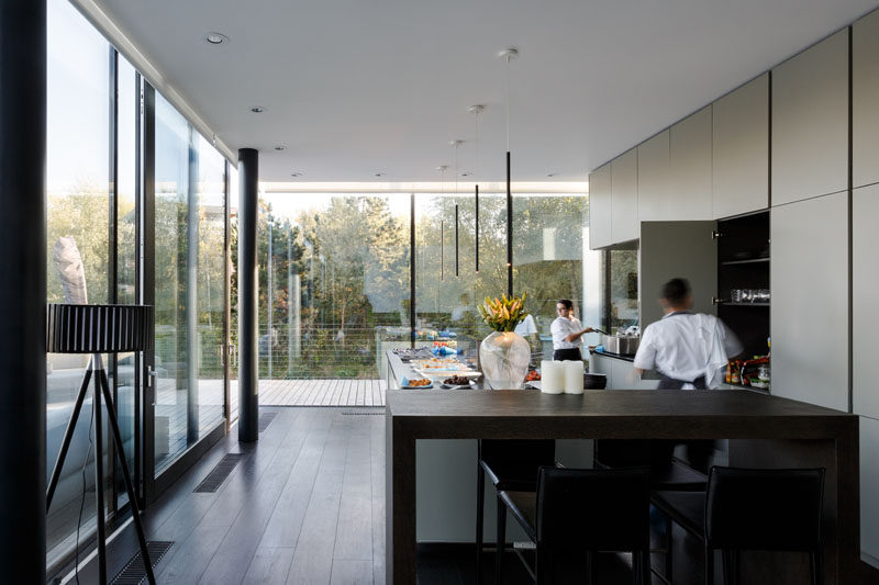 The glass corner windows in this modern kitchen give the feeling of living on the water, and large trees nearby provide privacy for the occupants. #Windows #KitchenDesign #InteriorDesign