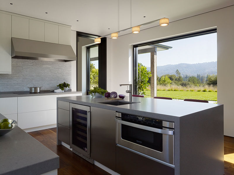 The large window in this modern kitchen perfectly frame the view of the garden and hills in the distance. #ModernKitchen #KitchenDesign #Windows