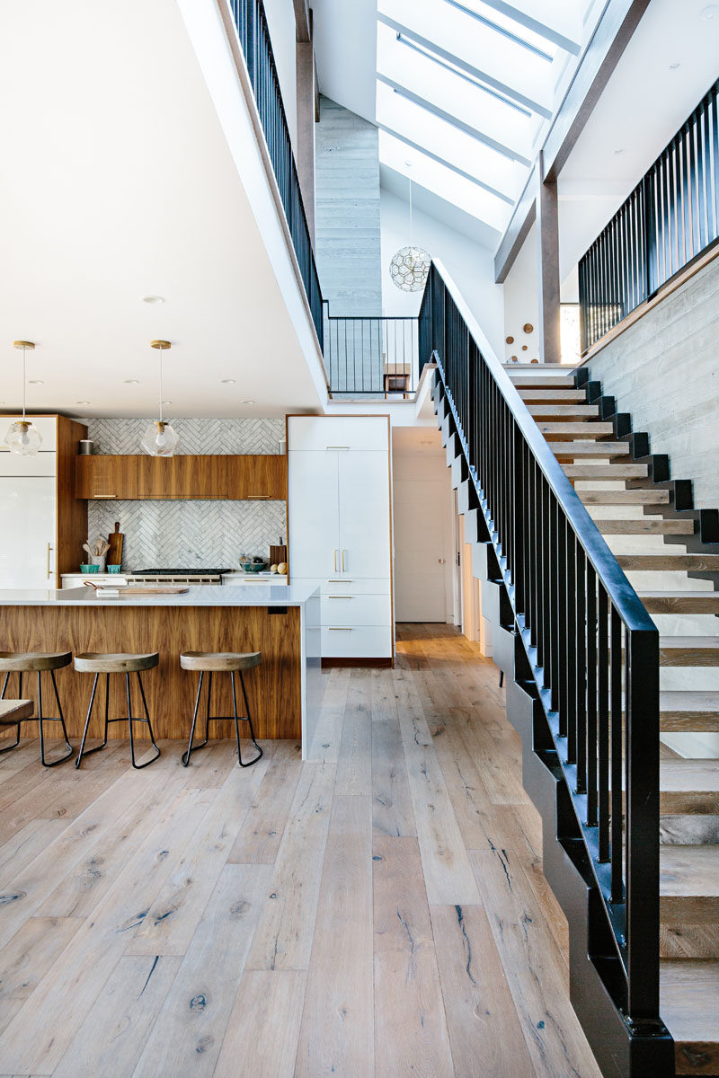 In this modern lake house, a tiled backsplash in a herringbone pattern adds a decorative touch to the kitchen, while wood and steel stairs lead to the upper floor of the home. #InteriorDesign #Kitchen #Stairs