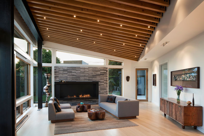 This modern living area is enclosed by a continuous glass wall, protected by a 6-ft roof overhang. #LivingRoom #Fireplace