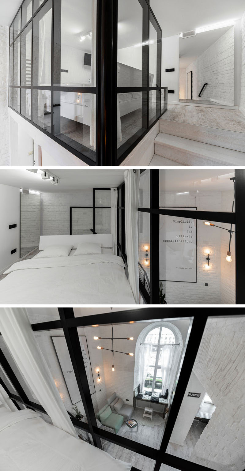 This modern mezzanine bedroom has a black-framed glass wall that overlooks the living room below. #Bedroom #ModernBedroom #GlassWall #MezzanineBedroom