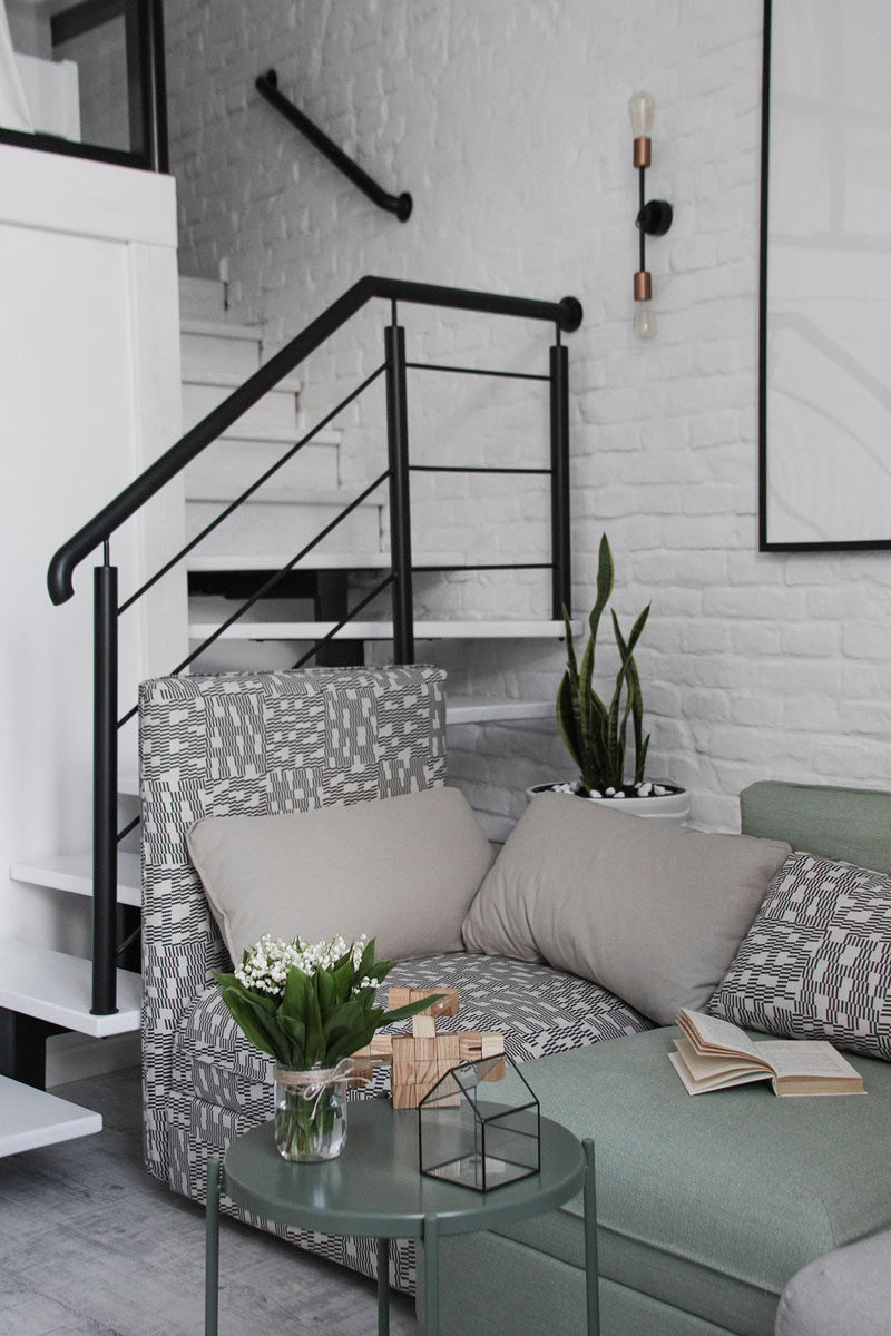 Black steel stairs with white treads lead up to the mezzanine level of this modern loft apartment. #Stairs #Staircase #StairDesign