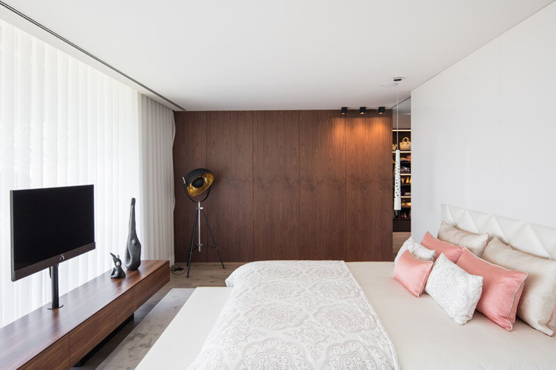 In this modern master bedroom, a wood accent wall adds a natural touch to the mostly white room. #MasterBedroom #WoodAccentWall