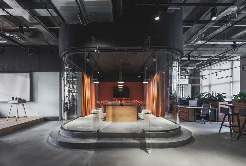 This modern office in Russia features a meeting room that's slightly raised and enclosed in a room with curved glass walls. #ModernOfficeDesign #OfficeInterior