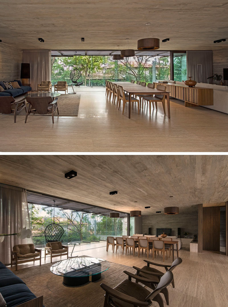 This modern house has a large open plan room that's home to a sitting area, a large dining table, and lounge with a large comfortable couch focused on the television. #ModernInteriorDesign #LivingRoom #ModernHouseInterior