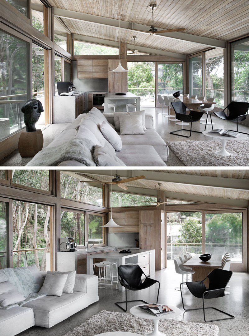 The living room of this modern house opens to the open plan dining room and kitchen. A sloped wood adds a natural warmth to the interior, while floor-to-ceiling windows capture the view of the surrounding trees. #ModernInteriorDesign #WoodCeiling #ConcreteKitchen
