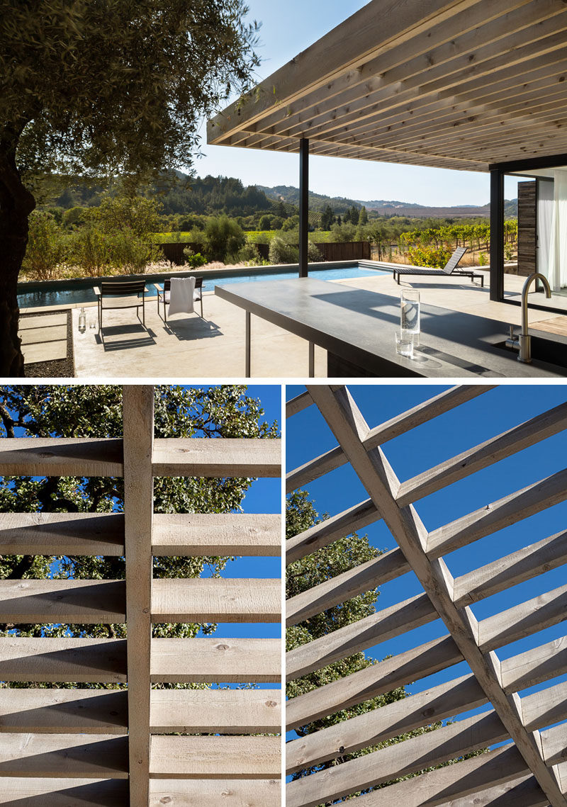 Large sliding doors connect the interior spaces of this modern pool house with the semi-covered outdoor terrace, that has an outdoor kitchen and views of the surrounding area. #Pergola #PoolHouse