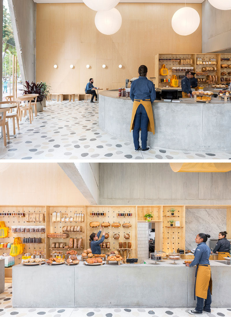 In this modern restaurant / cafe, a curved concrete service counter that extends into a straight bar area, provides the employees with plenty of room to display and sell goods. #InteriorDesign #RetailDesign #Cafe #Restaurant