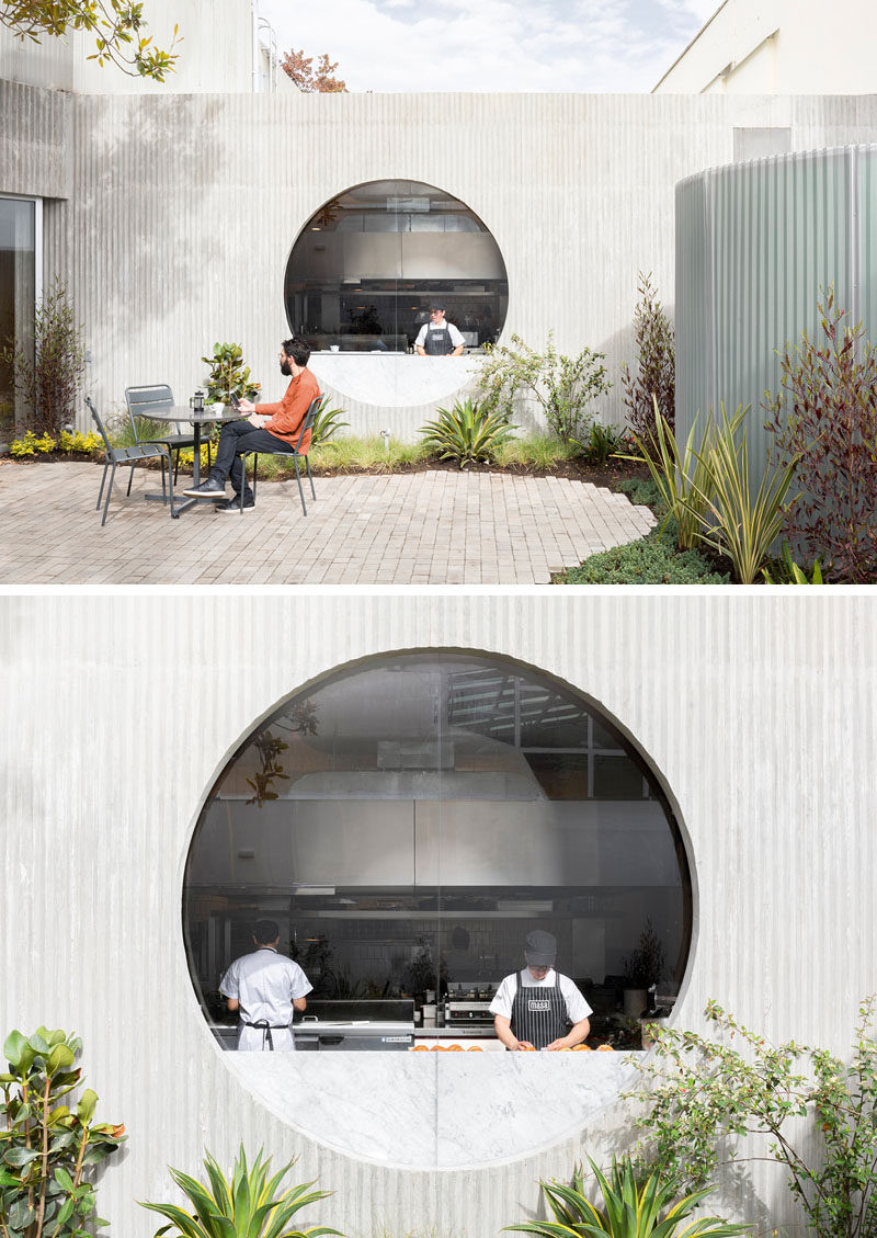 In this restaurant's courtyard, there's a stone patio with seating, that's surrounded by curved landscaping, while a round window provides a glimpse into the kitchen. #Courtyard #Window #Restaurant