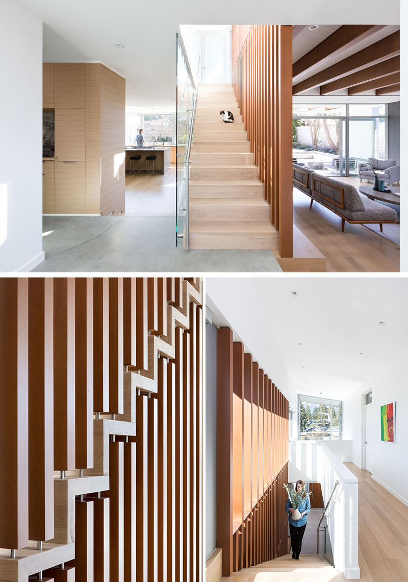 This modern and open staircase uses wood verticals to carry the eye upwards to the second floor, while large window runs the full width of the stair on the second level and allows light to enter deep into the center of the home. #Stairs #Staircase #WoodStairs #ModernStairs