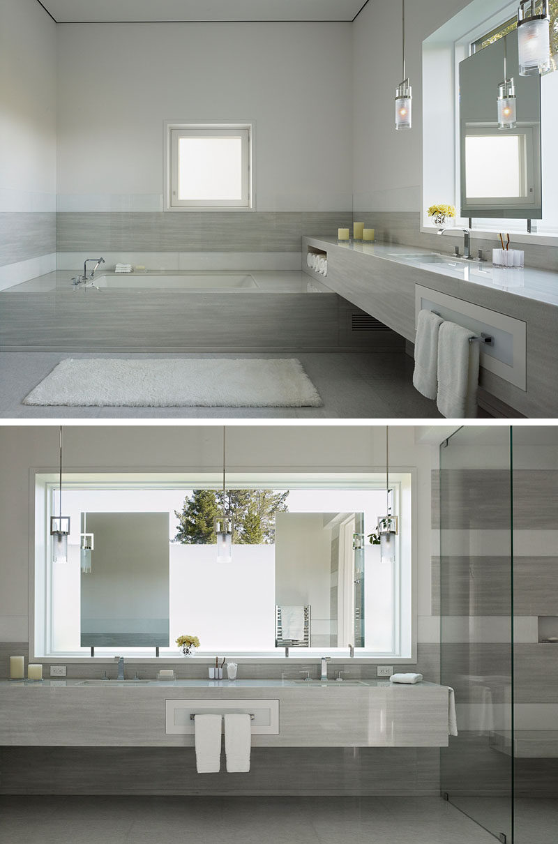 In this modern bathroom, crisp white walls have been paired with polished surfaces, dramatic lighting, and frosted windows for a contemporary appearance. #BathroomDesign #ModernBathroom