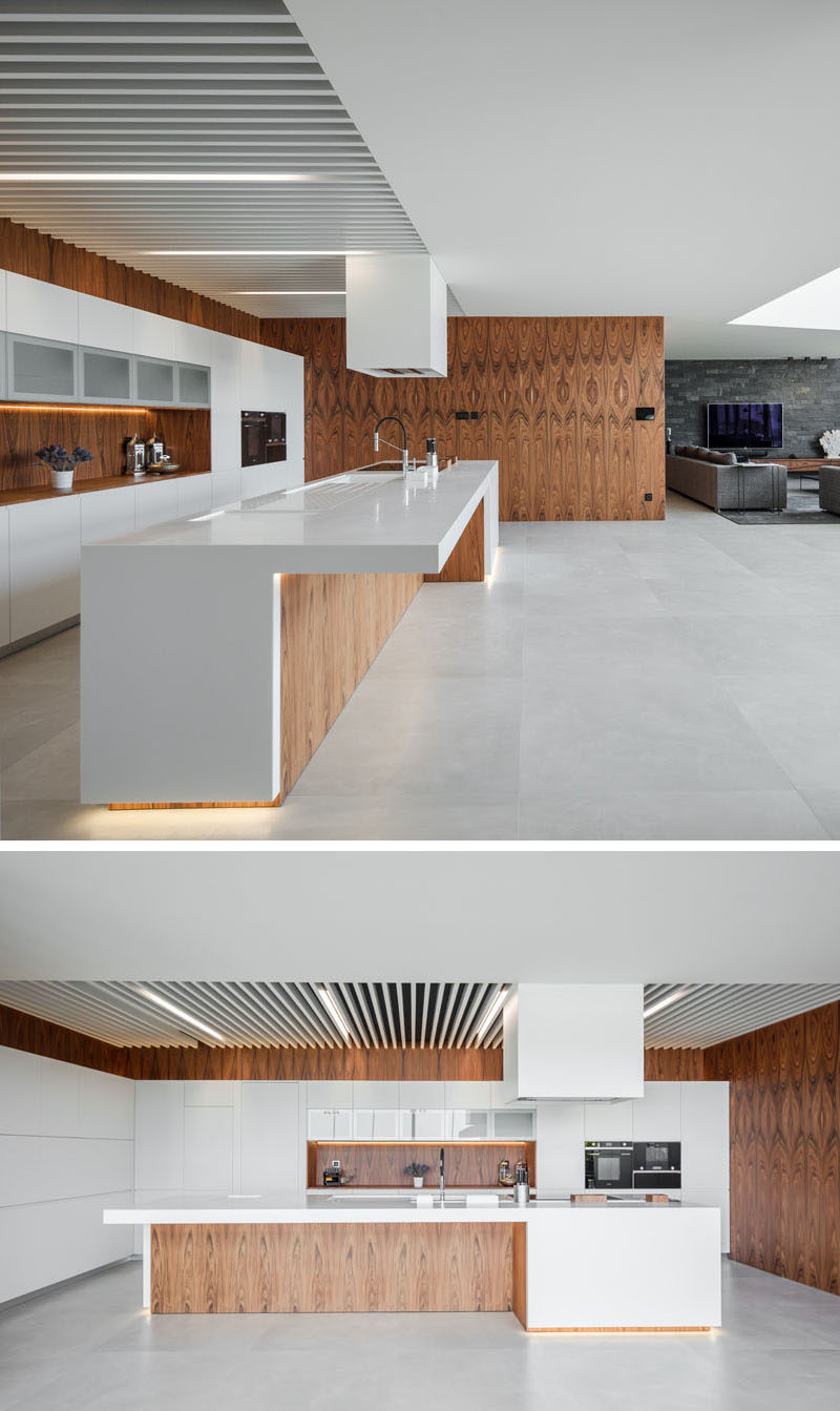 The open plan interior of this modern house allows for easy movement between the different social areas of the house, while the kitchen is defined by the use of wood walls that provide a backdrop for the white cabinets. #ModernKitchen #WoodAndWhiteKitchen #KitchenDesign
