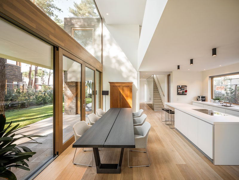 This modern house has a double-height ceiling above dining table, large windows for plenty of natural light, and wood framed sliding doors to connect to the outdoors. #DiningRoom #WhiteKitchen #DoubleHeightCeiling #Windows #SlidingDoors