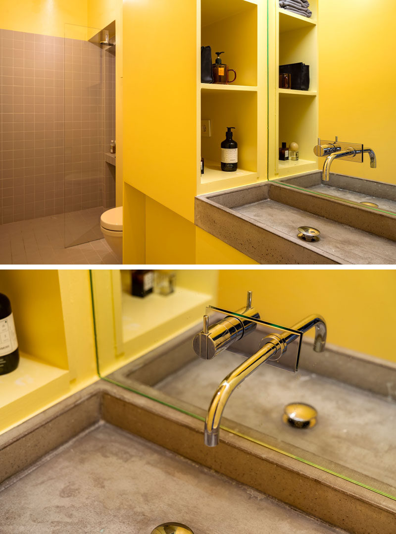 This modern bathroom features yellow walls and cabinetry, and a concrete sink. #BathroomDesign #YellowBathroom