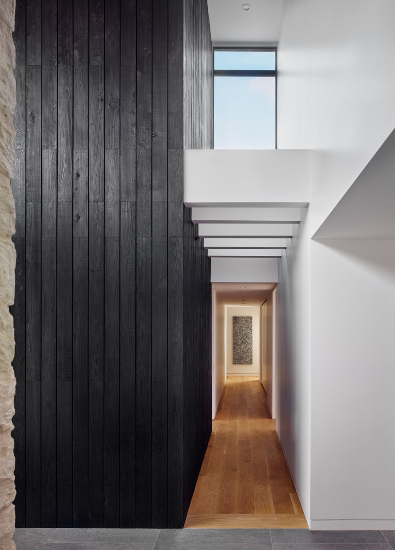 Inside this modern home, a double-height vaulted entryway with a shou sugi ban accent, welcomes guests and guides them to the various areas of the house. #ShouSugiBan #Hallway