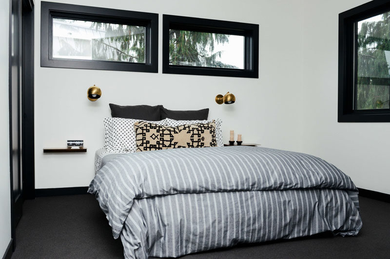 In this contemporary bedroom, simple floating shelves and single sconces have been placed on either side of the bed, while dark flooring contrasts the white walls. #Bedroom #ModernBedroom