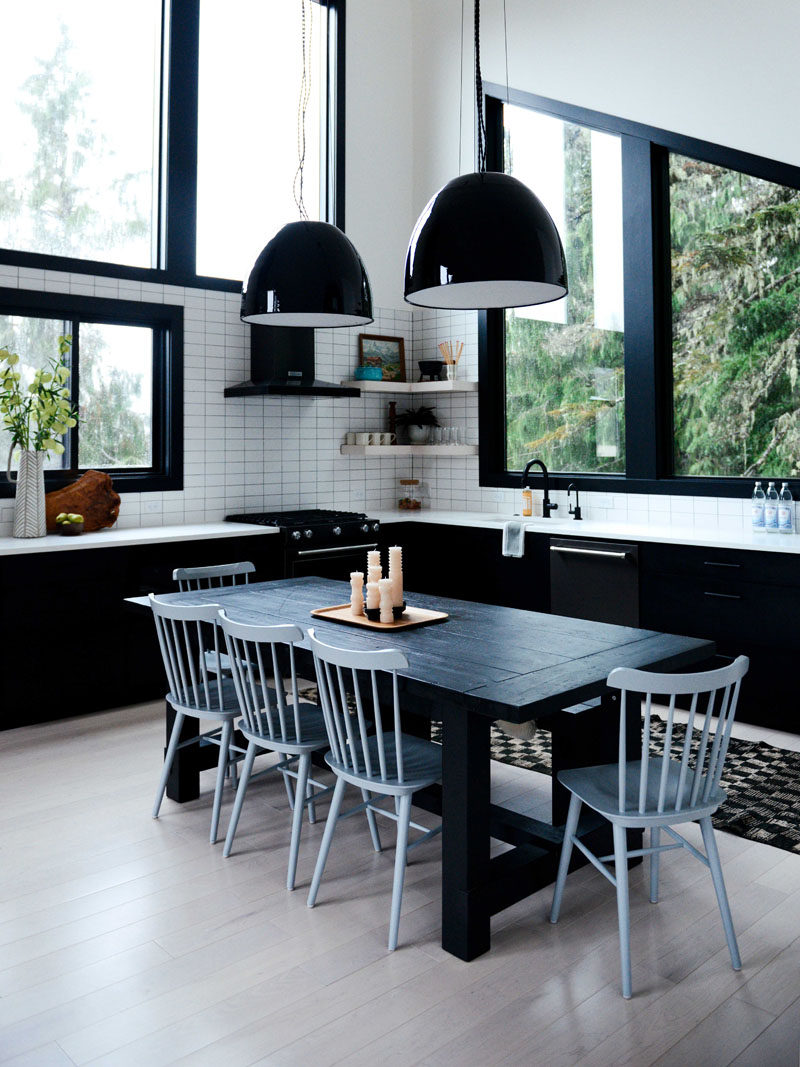 In this contemporary kitchen, lower black cabinets tie in with the black dining table, while white tiles and open corner shelving has been installed on the walls. #KitchenDesign #BlackAndWhiteKitchen