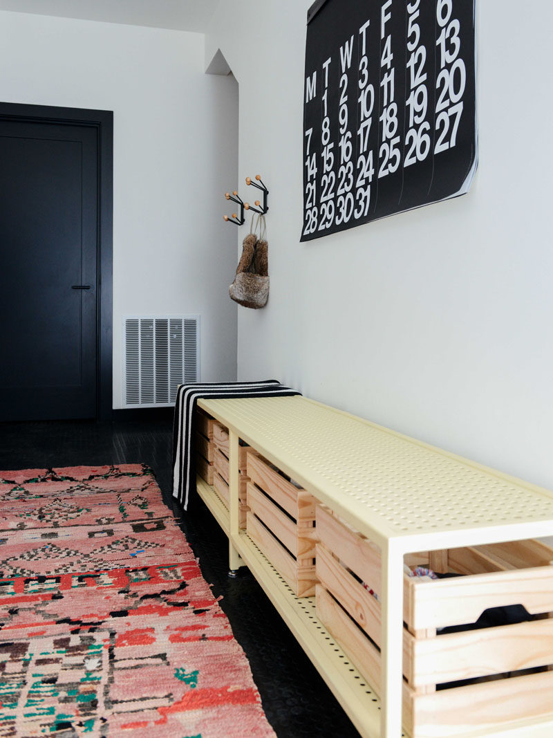 A colourful rug adds warmth to this contemporary entryway that features black flooring and a steel bench with wood cubbies. #Entryway #InteriorDesign