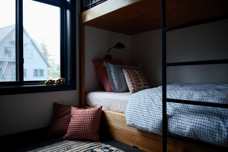 In this modern kids room, there's a set of wood bunk beds with a minimalist black ladder. #BunkBeds #KidsRoom #Bedroom