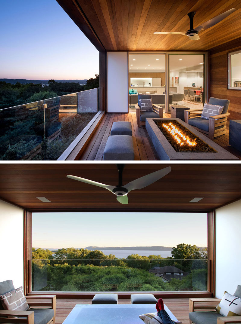 This modern house has a covered outdoor area, that's furnished with a couple of armchairs and a fire table. Glass handrail's allow for an uninterrupted water views. #ModernOutdoorSpace #Modernhouse