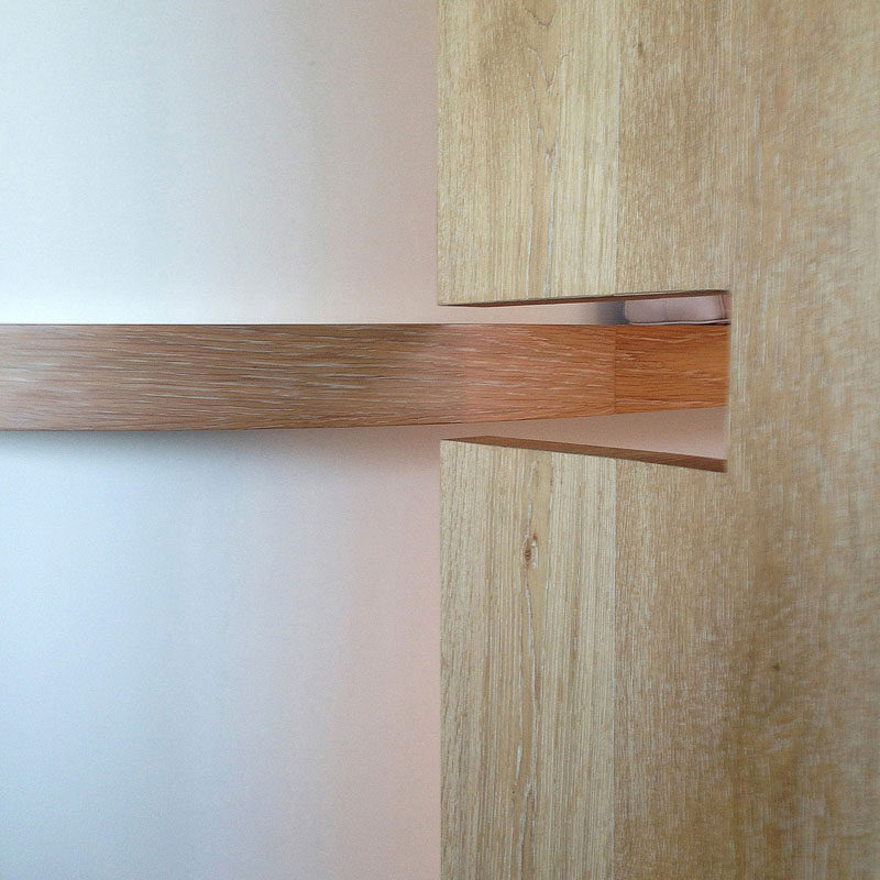 This modern Australian house features a large wooden pocket door that has a small cutout for a shelf that wraps around the wall. #PocketDoor #Door #WoodDoor #Shelf #CurvedShelf