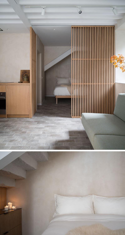 This minimalist bedroom is somewhat hidden behind a sliding wood slat screen, conserving space andcreating a secluded sleeping area. #Bedroom #WoodSlatScreen #SlidingDoor