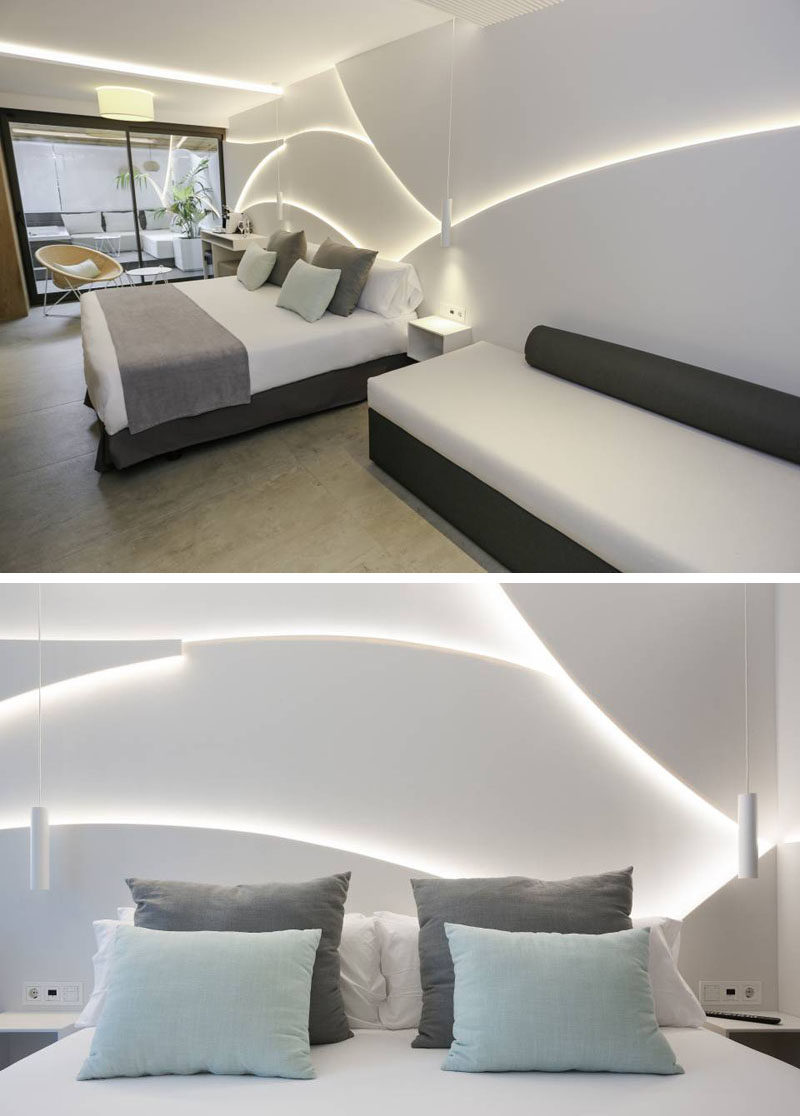 This modern and sculptural headboard (accent wall) was inspired by the swell of the sea, and they achieved this by superimposing several panels made from HI-MACS and combining it with hidden LED lighting. #Bedroom #Headboard #AccentWall