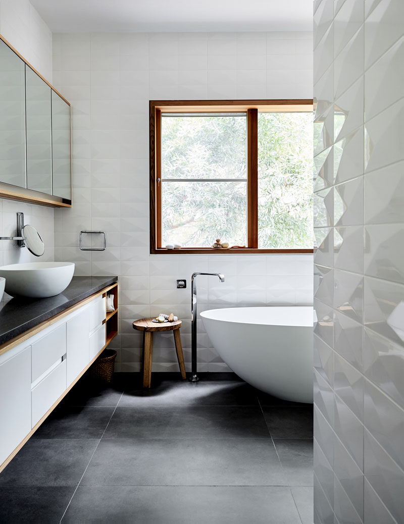 In this modern bathroom, the walls have been covered in a three-dimensional white tile, creating visual interest and contrasting the grey tiles and vanity counter. #BathroomDesign #ModernBathroom