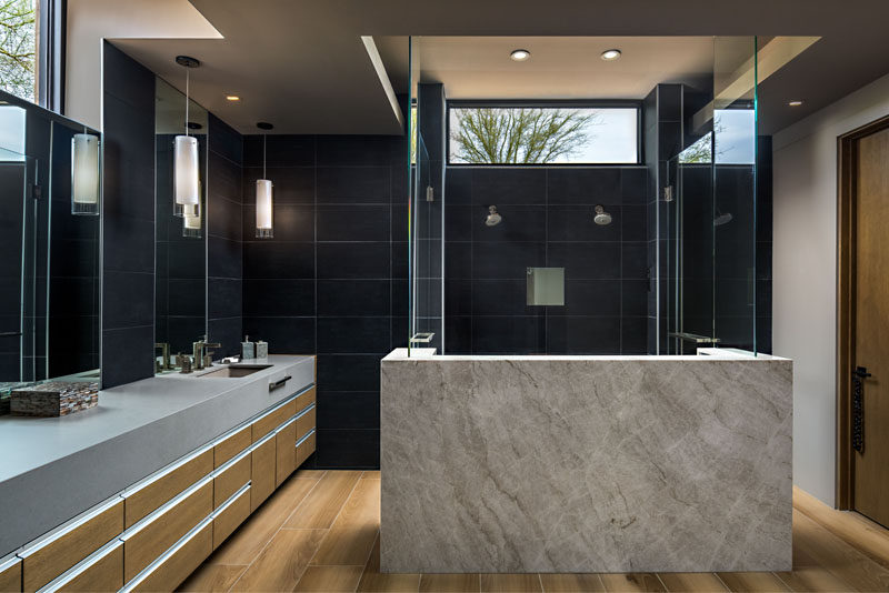 In this modern master bathroom, dark tiles cover the walls, while a walk-in two-person shower draws attention from anyone walking into the bathroom. #BathroomDesign #ModernBathroom