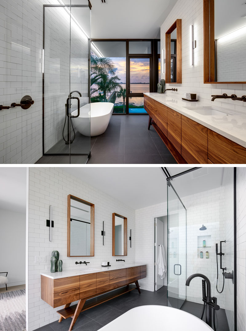 In this modern bathroom, the freestanding bathtub is positioned for water views, while the wood framed mirrors and the wood vanity add a natural touch to the white and grey bathroom. #ModernBathroom #BathroomDesign