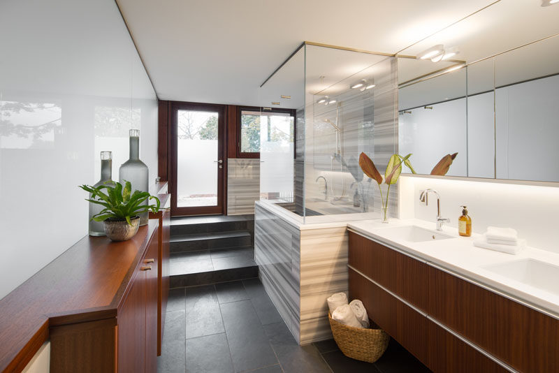 In this modern bathroom, wood cabinetry adds a natural touch, while a partially frosted door provides access to the outdoors. #BathroomDesign #ModernBathroom