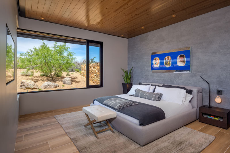 In this modern bedroom, a grey accent wall creates a calming atmosphere, while the windows perfectly frame the trees outside. #BedroomDesign #ModernBedroom #Windows