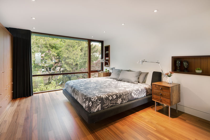 In this modern bedroom, wood-lined shelving has been built into the wall, while opposite the bed is a wall full of cabinetry. #Bedroom #Shelving