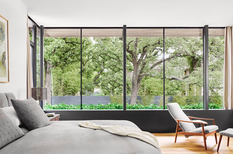 This modern bedroom features a wall of windows that overlook the trees outside. #Bedroom #Windows
