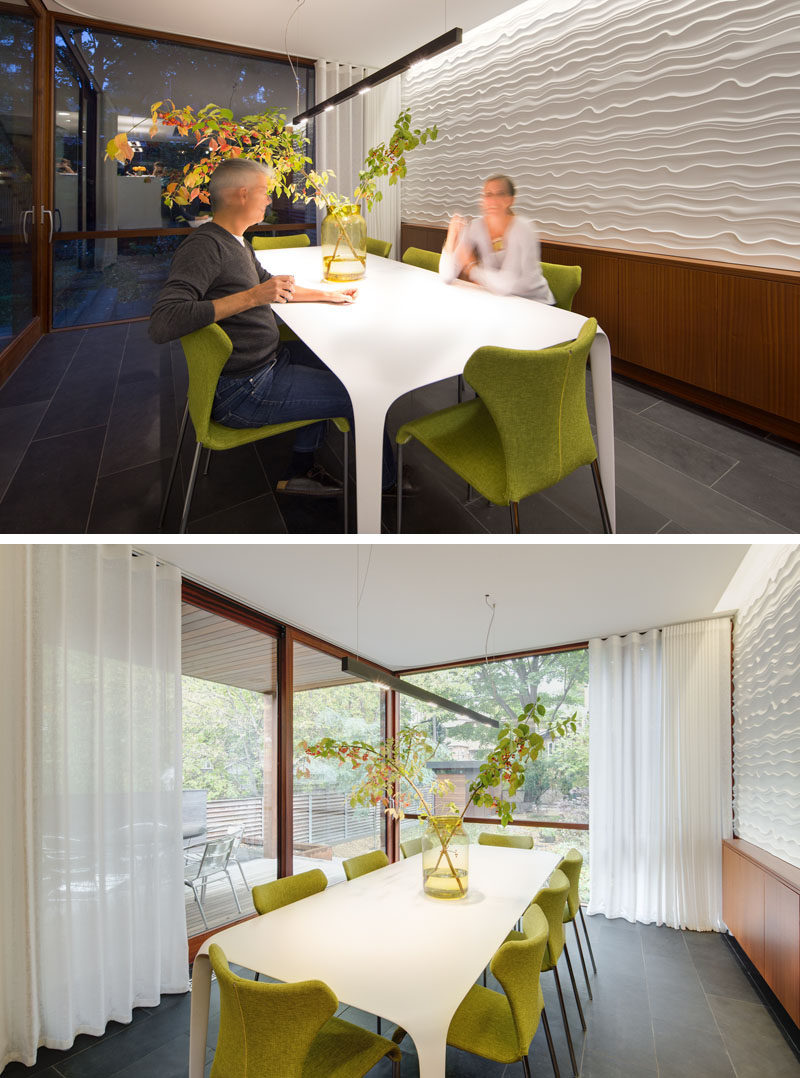 This modern dining room has a textured wall, and floor-to-ceiling windows overlooking the backyard. #DiningRoom #ModernDiningRoom