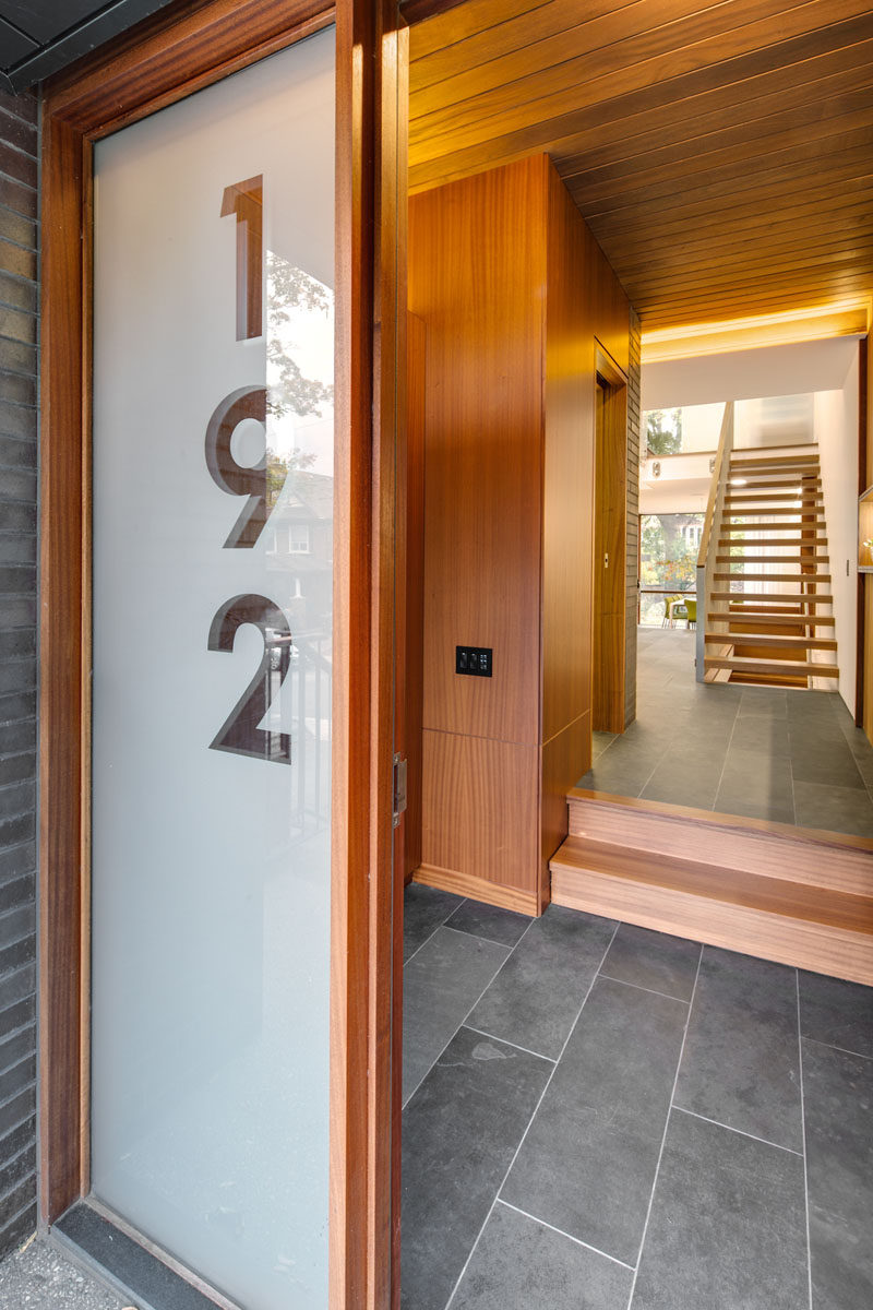 This front door, with an adjacent large glass panel showcasing the house number, guides visitors into the home. #FrontDoor