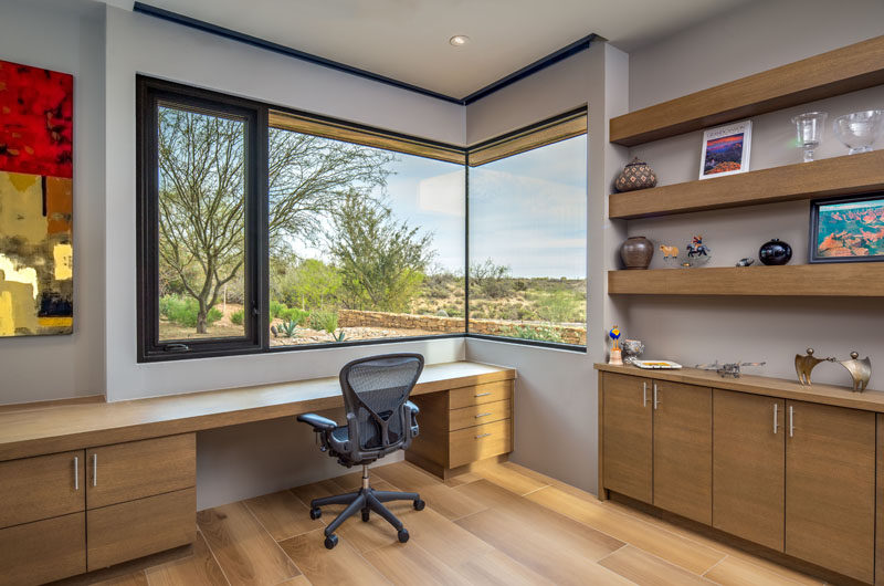 This modern home office has open shelving, wood cabinetry, and a window that wraps around the corner of the room. #HomeOffice #Window
