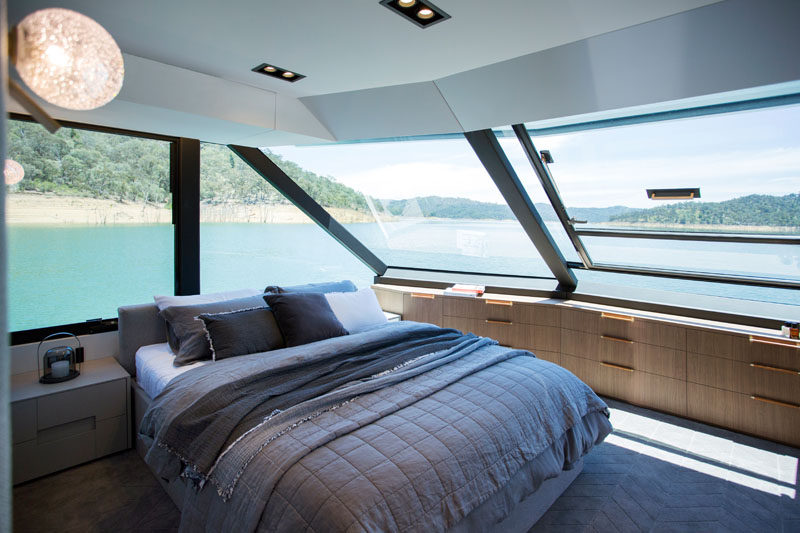 The master bedroom of this modern houseboat has wrap around windows, and plenty of built-in storage. #Bedroom #Houseboat