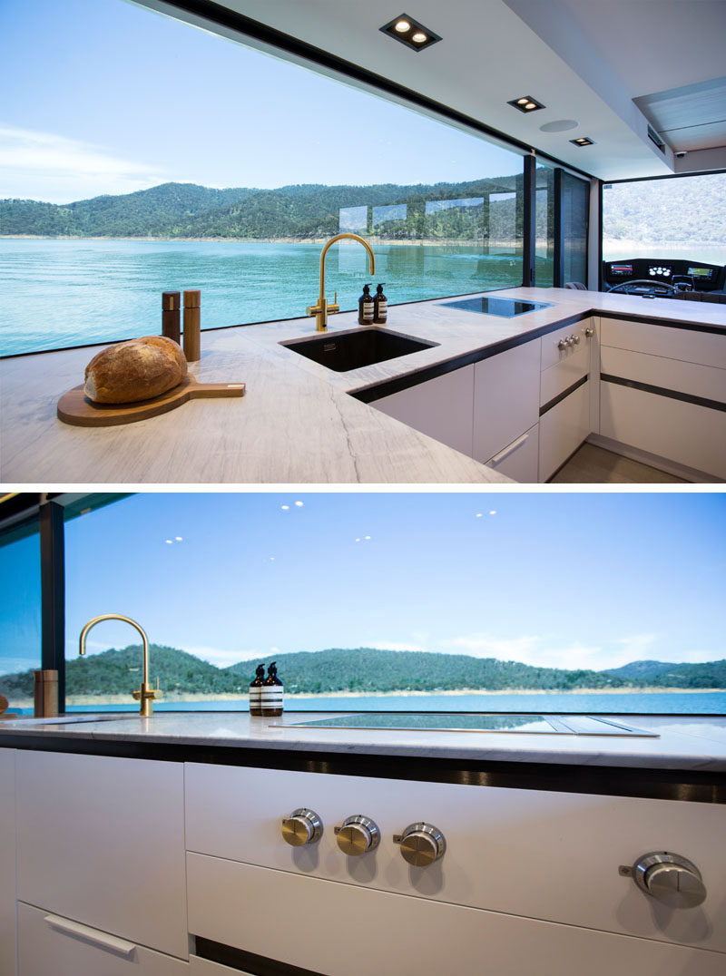 In the houseboat kitchen, a large picture window perfectly frames the views, while the cabinetry has a minimalist appearance. #Houseboat #ModernKitchen #PictureWindow
