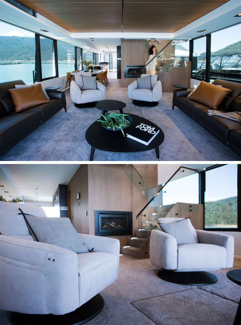 Large windows surround all of the interior spaces of this modern houseboat, like the living room. Couches on either side face opposite windows, while two armchairs look out towards the rear of the houseboat. #LivingRoom #Houseboat