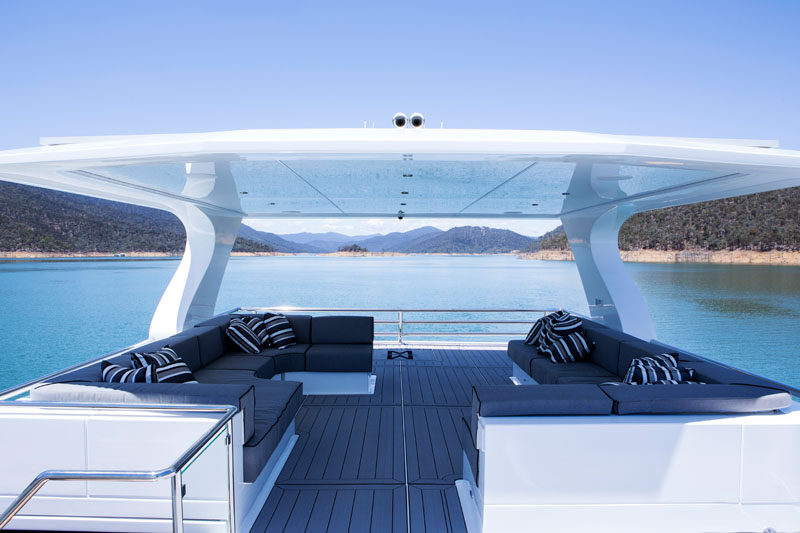 On the top of this modern houseboat, there's outdoor space in the form of a covered rooftop lounge, with couches that wrap around the corners. #Rooftop #Houseboat #OutdoorLounge