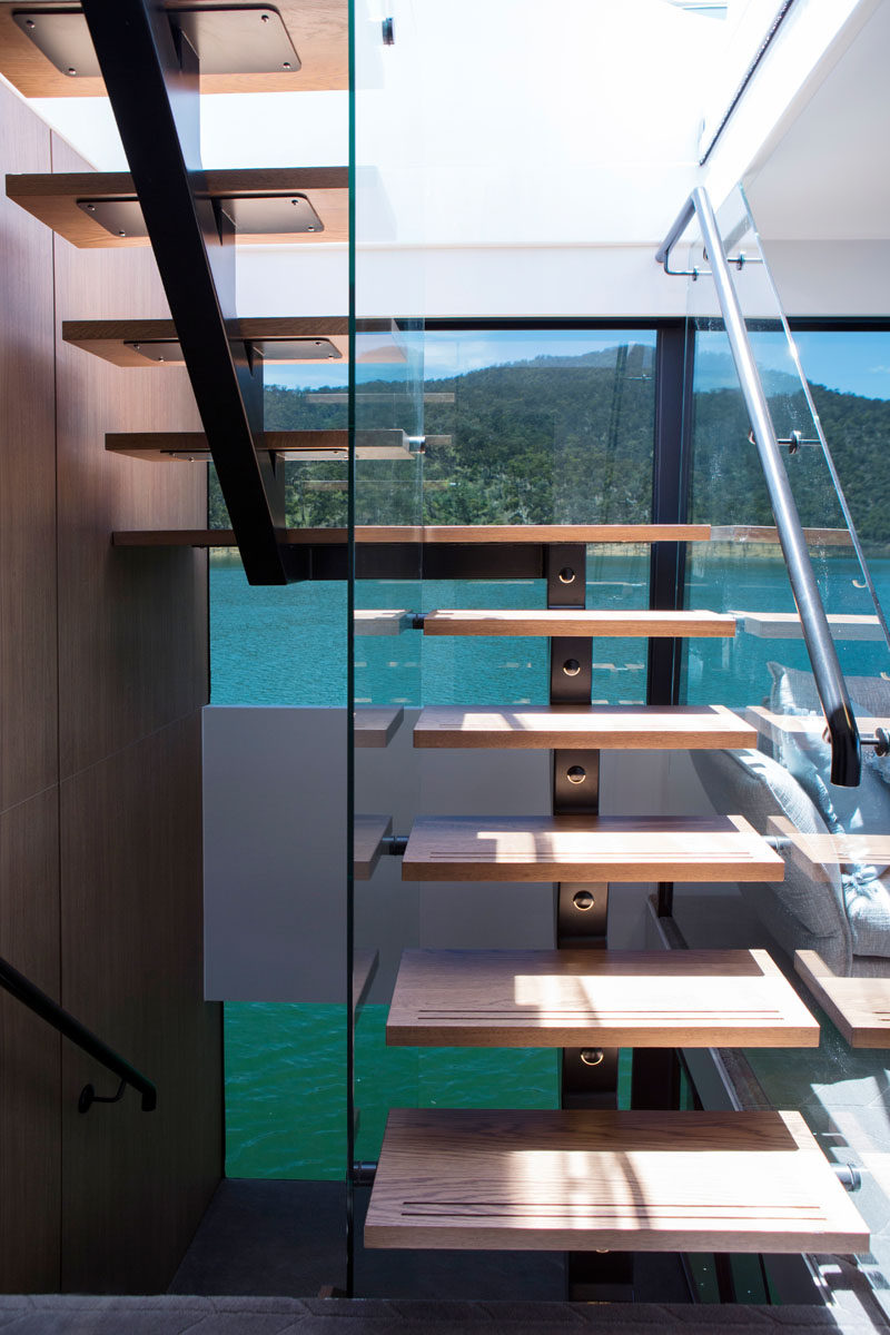 Wood stairs with steel supports connect the various levels of this modern houseboat. #Houseboat #ModernStairs