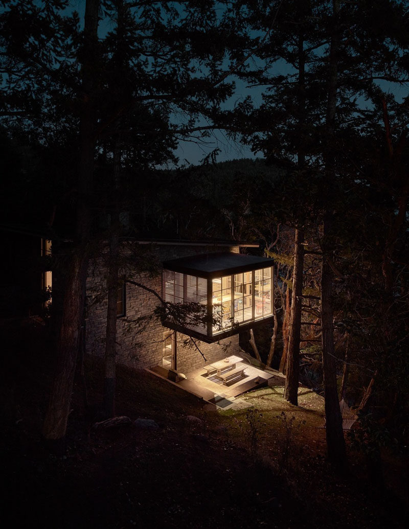 This guest house features a dining room that was conceived as a three-sided glass object floating in a forest of trees. Below the dining room, there's an alfresco dining area that's lit from lights underneath the cantilevered dining room above. #Cantilever #Architecture #DiningRoom
