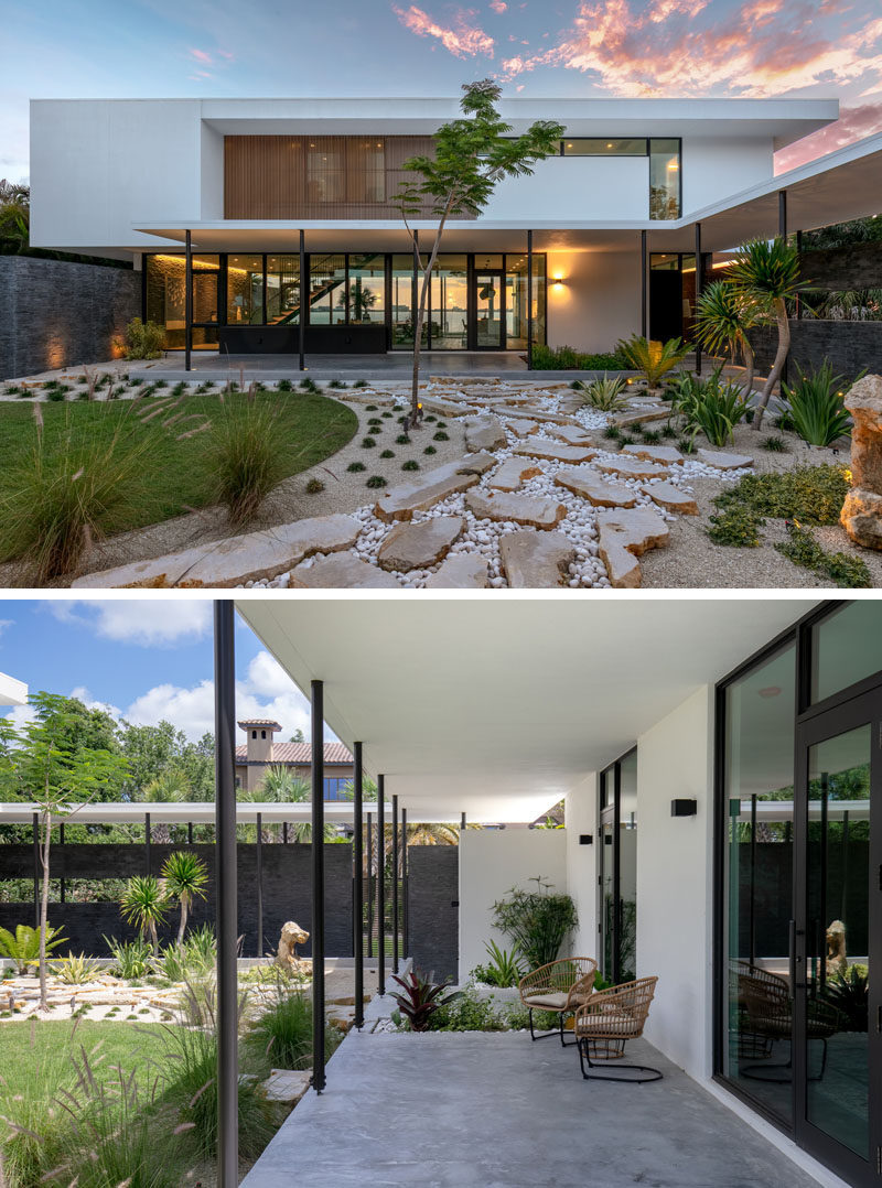 This modern house has a landscaped courtyard with stone and a small lawn, contrasts thedark limestone walls. #Landscaping #HouseDesign