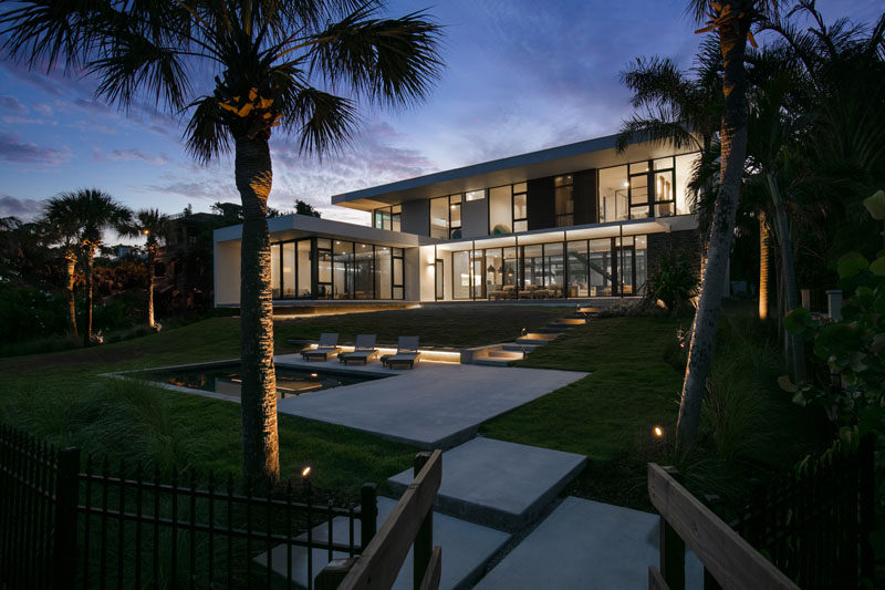 This modern house has steps that lead down to the swimming pool and deck. #ModernHouse #Landscaping #SwimmingPool