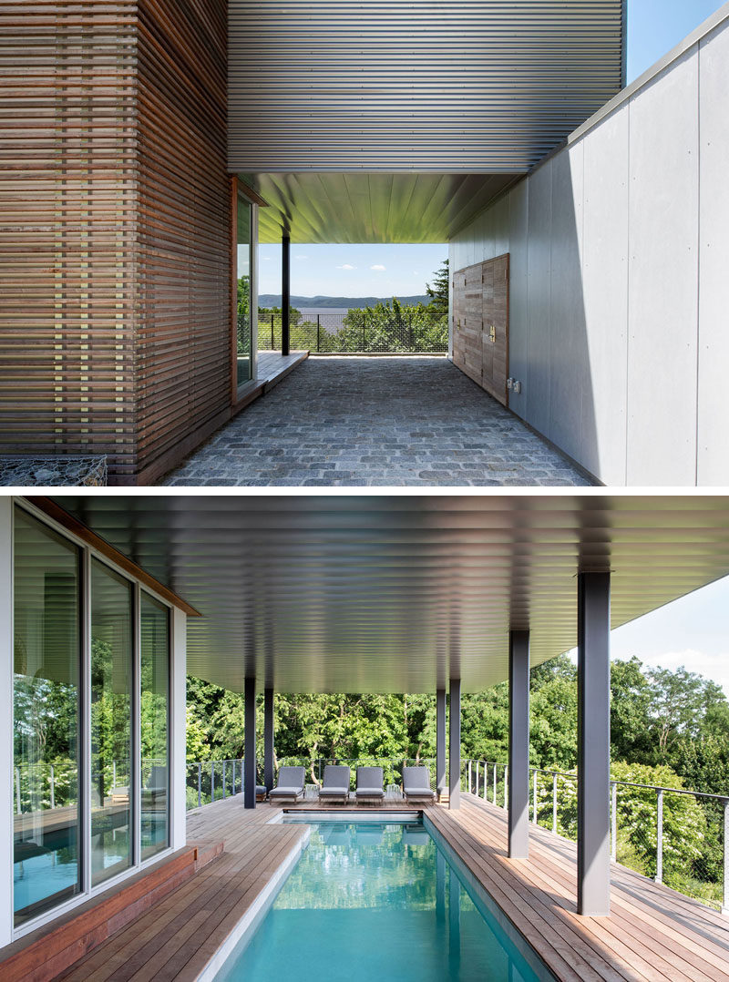 The entry to this modern house is tucked away beside the covered carport, that features metal panels that extend to cover the adjacent swimming pool and deck. #ModernHouse #Carport #SwimmingPool #Deck