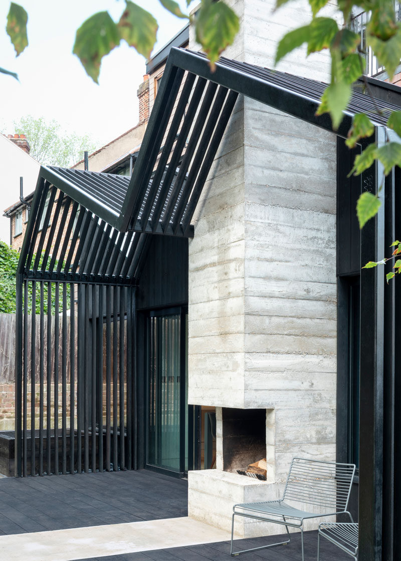 The dark exterior of this contemporary extension is contrasted by a ribbon of board-formed concrete that highlights the fireplace. #OutdoorFireplace #ExteriorFireplace
