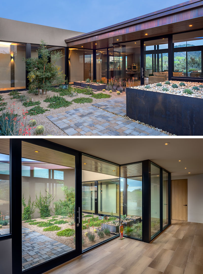 A small courtyard with a simple garden, steel planter boxes, and a stone path, leads to the glass front door of this modern house. #Landscaping #GlassWalls #GlassFrontDoor